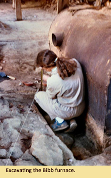 Image of an archaeologist exacating the bibb flue inside the Parran barn.