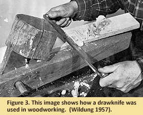 Photo of man using drawknife.